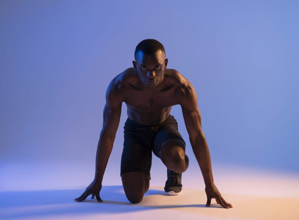 Sprinter African Muscular Man in blue light preparing for the start.
